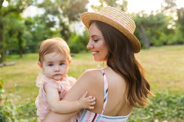 Jovem mãe sorridente com sua filha no parque