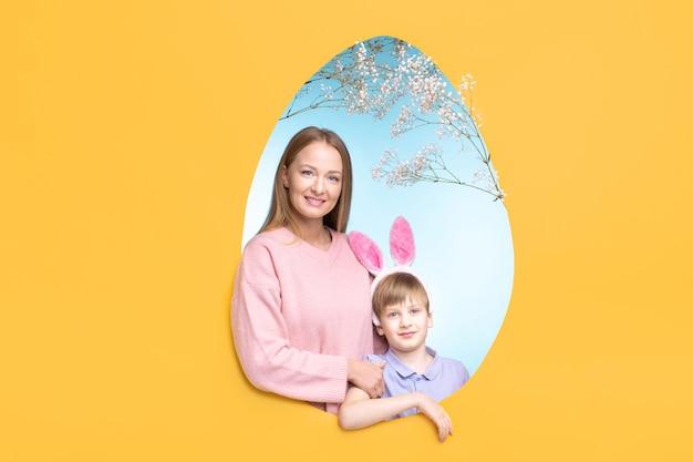 Jovem mãe sorridente e filho fofo com uma faixa de orelhas de coelho, posando em uma moldura em forma de ovo para cartão de páscoa familiar