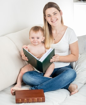 Jovem mãe sorridente olhando as fotos do álbum