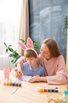 Jovem mãe sorridente, sentada à mesa, ajudando o filho a assinar o cartão de páscoa com tinta