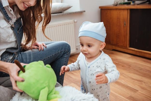 Jovem mãe sorridente, sentada e brincando com seu filho pequeno em casa