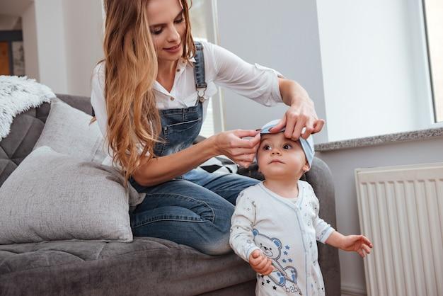 Jovem mãe sorridente, sentada no sofá e cuidando do filho pequeno em casa