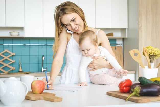 Jovem mãe sorrindo, cozinhando e brincando com sua filha bebê em uma cozinha moderna. usando o telefone trabalhando em casa.