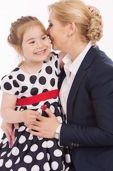 Jovem mãe sussurra para a filha no ouvido