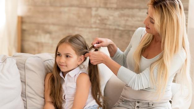 Jovem mãe trançando o cabelo da filha