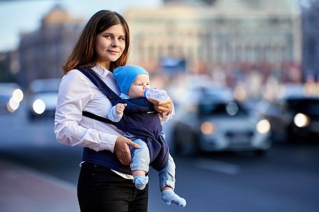 Jovem mãe usa tipoia de bebê para passear ao ar livre com seu filho