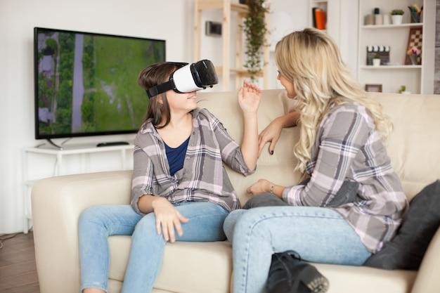 Jovem mãe usando aparelhos modernos para sua educação de menina. óculos de realidade virtual.