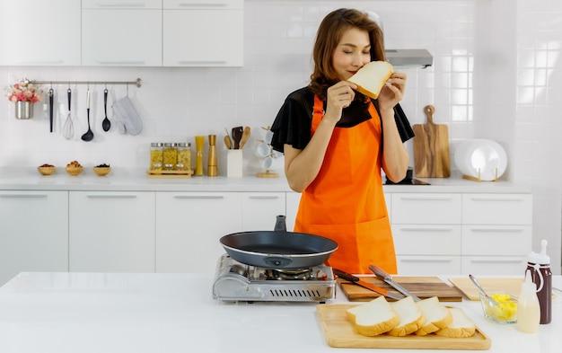 Jovem mãe usando avental laranja na cozinha moderna de casa e preparando pão grelhado com uma cara feliz.