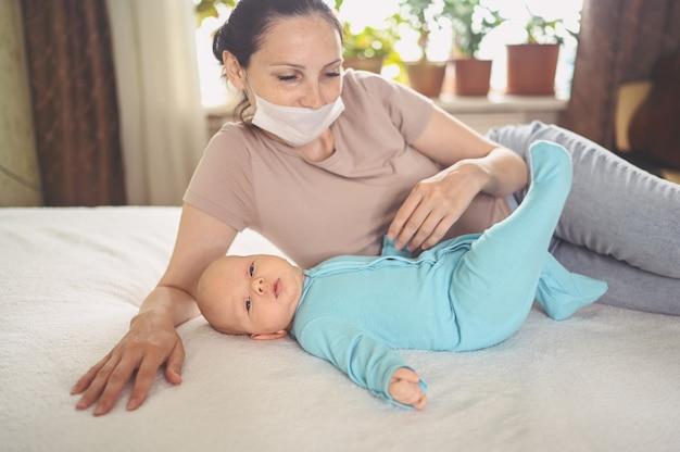 Jovem mãe usando máscara protetora com um bebê recém-nascido fofo em macacão azul, abraçando-o deitado na cama