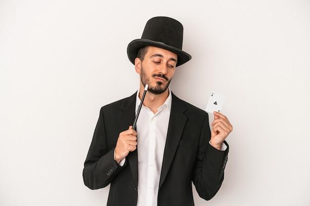 Jovem mágico segurando uma varinha e um cartão mágico isolado no fundo branco