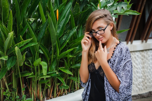 Jovem magra em uma vila tropical em bali, usando óculos e lingerie