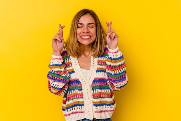 Jovem magrela caucasiana isolada na parede amarela cruzando os dedos para ter sorte