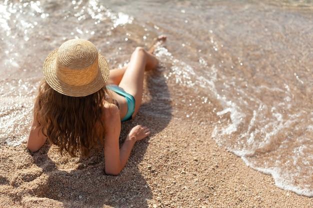 Jovem magrela de chapéu, deitada na praia, na areia amarela, perto da onda do mar. vista de cima linda garota.