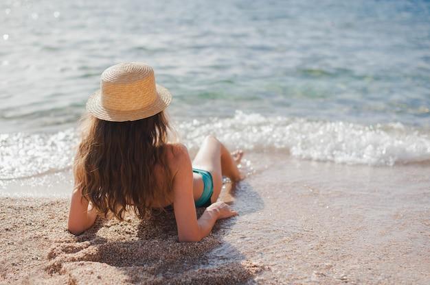 Jovem magrela de chapéu, deitada na praia, na areia amarela, perto da onda do mar. vista de cima linda garota
