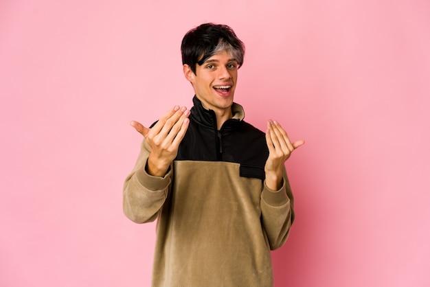Jovem magrelo hispânico apontando com o dedo para você como se fosse um convite para se aproximar