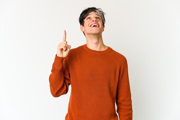 Jovem magrelo hispânico indica com os dois dedos dianteiros para cima mostrando um espaço em branco