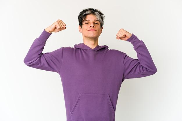Jovem magrelo hispânico mostrando força gesto com os braços, símbolo de poder