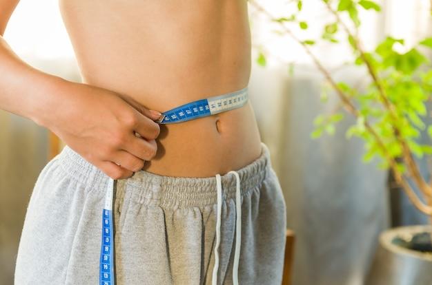 Jovem magrinha medindo a cintura fina com uma fita métrica