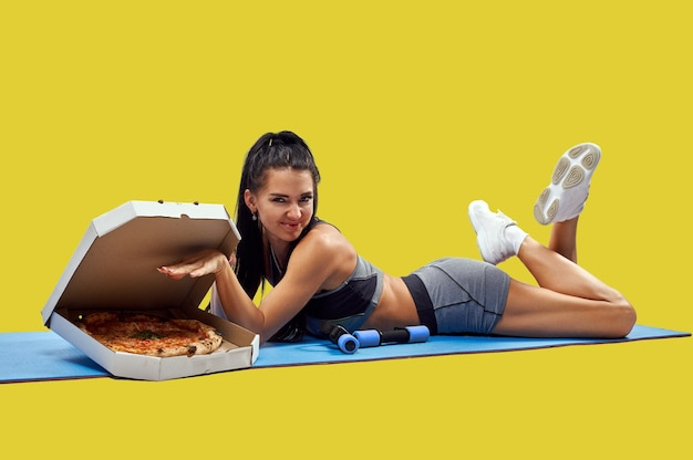 Jovem magro apto deitado sobre um tapete de fitness perto de uma caixa com saborosa pizza fresca. isolado. conceito de corpo saudável e junk food. conceito de perder peso e engordar