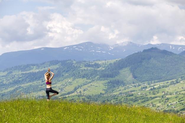 Jovem magro atraente fazendo exercícios de ioga ao ar livre