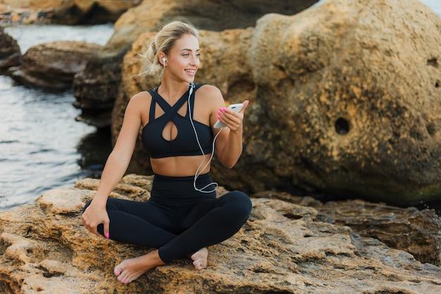 Jovem magro cabe mulher no sportwear ouvindo música em fones de ouvido e usando o smartphone enquanto está sentado em uma pedra em uma praia selvagem
