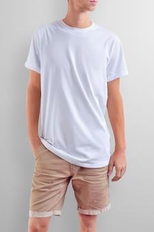 Jovem magro caucasiano em uma camiseta em branco e shorts marrom de algodão em um fundo branco do estúdio. pose frontal. a maquete pode ser usada em seu design.