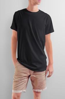 Jovem magro caucasiano em uma camiseta preta e shorts marrom de algodão em um fundo branco de estúdio