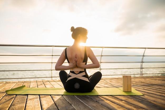 Jovem magro e atraente fazendo ioga pela manhã, no nascer do sol, à beira-mar