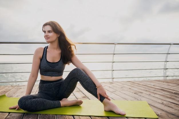 Jovem magro e bela mulher atraente relaxando em um tapete de ioga pela manhã, ao nascer do sol no mar, estilo de vida saudável, esporte fitness