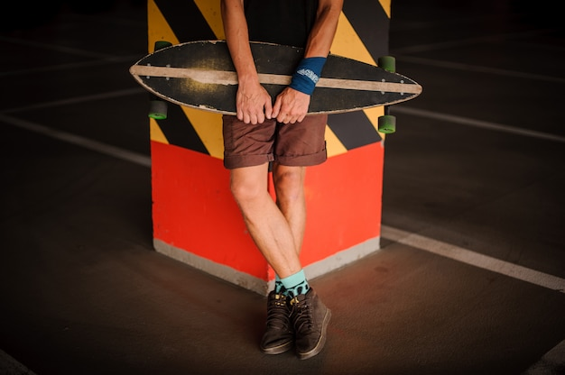 Jovem magro em shorts segurando um longboard