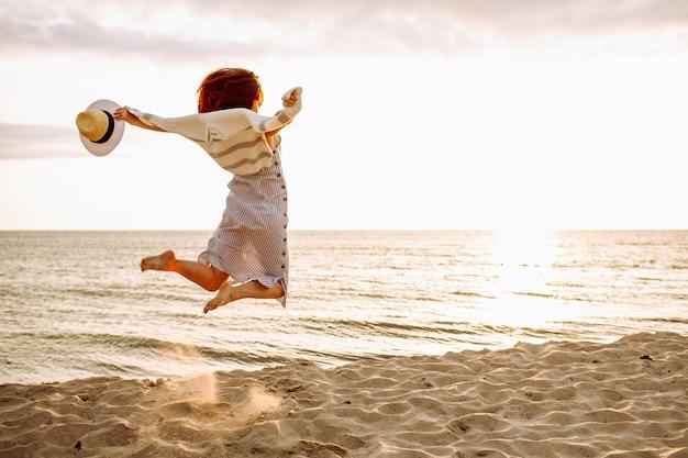 Jovem magro em um vestido de verão pulando na praia ao pôr do sol. liberdade, perda de peso, conceito de férias de verão.