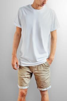 Jovem magro em uma camiseta em branco e shorts de algodão marrom em um fundo branco do estúdio. pose frontal. o modelo pode ser usado em seu design.