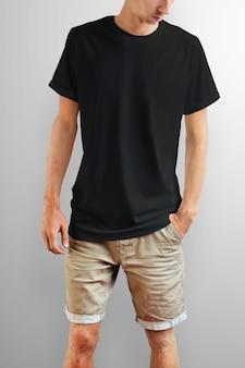 Jovem magro em uma camiseta preta e shorts de algodão marrom em um fundo branco do estúdio. pose frontal. o modelo pode ser usado em seu design.