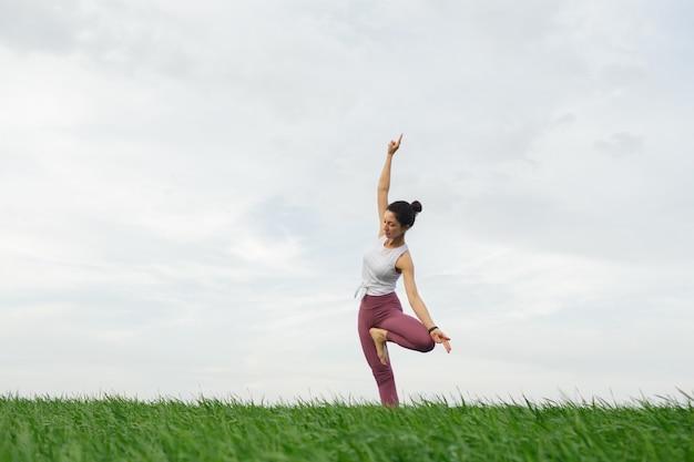 Jovem magro fazendo ioga ao ar livre em um campo verde