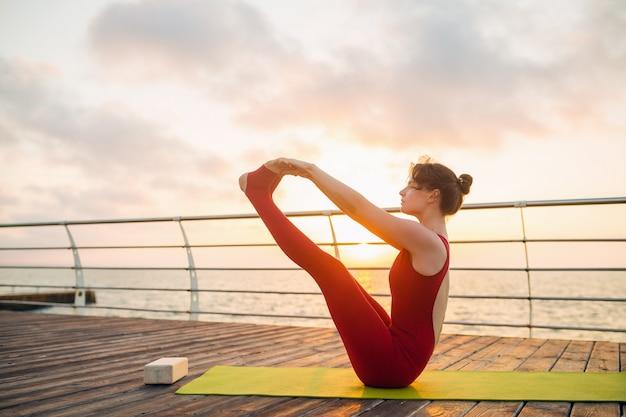Jovem magro mulher atraente bonita fazendo yoga de manhã no nascer do sol pelo mar, estilo de vida saudável
