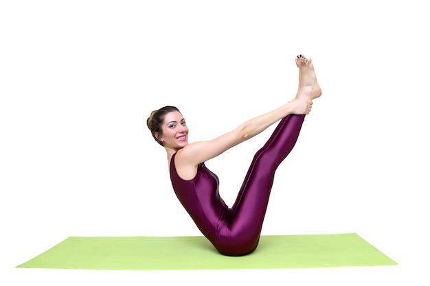 Jovem magro mulher praticando yoga no estúdio