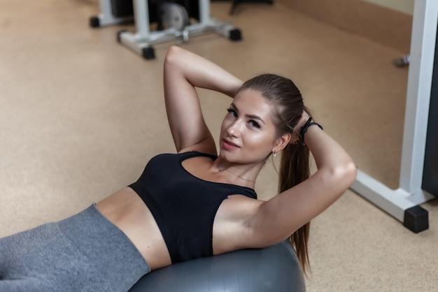 Jovem magro no sportswear está treinando os músculos abdominais na bola fit no ginásio