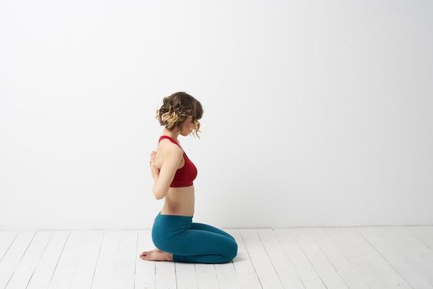 Jovem magro praticando ioga e exercícios em casa