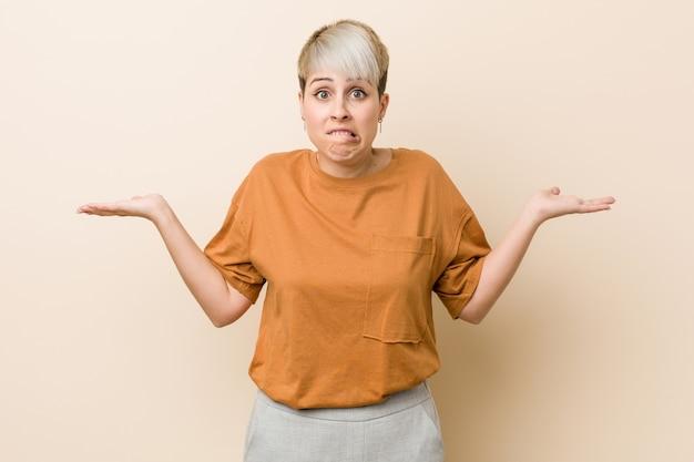 Jovem, mais mulher de tamanho com cabelo curto confuso e duvidoso encolher os ombros para segurar um espaço de cópia.