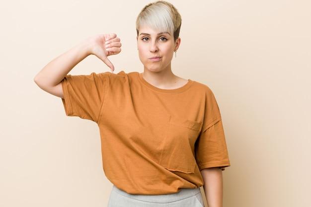 Jovem, mais mulher de tamanho com cabelo curto, mostrando um gesto antipatia, polegares para baixo. conceito de desacordo.
