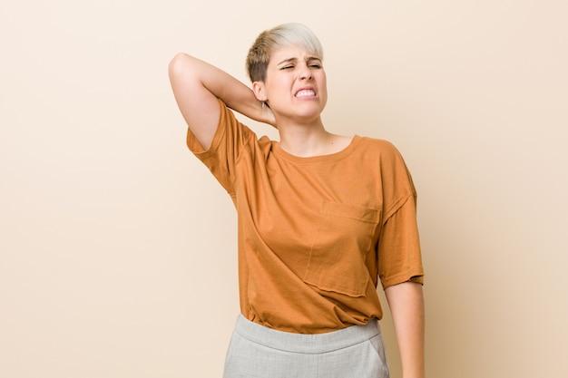 Jovem, mais mulher de tamanho com cabelo curto, sofrendo de dor no pescoço devido ao estilo de vida sedentário.
