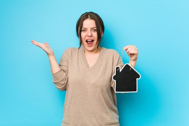 Jovem, mais tamanho mulher curvilínea segurando um ícone em casa comemorando uma vitória ou sucesso