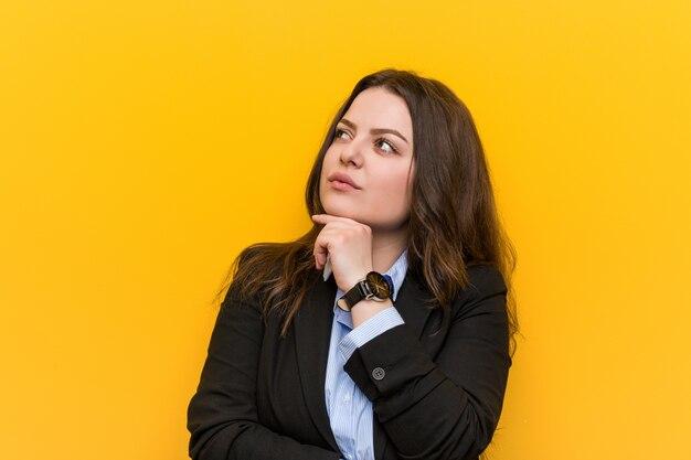 Jovem, mais tamanho mulher de negócios caucasiano olhando de soslaio com expressão duvidosa e cético.