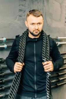 Jovem malhando com cordas de batalha em uma academia