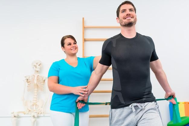 Jovem malhando com fisioterapeuta e faixa de resistência