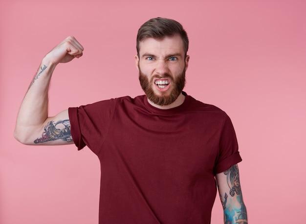 Jovem malvado homem barbudo vermelho em t-shirt em branco, fica sobre fundo rosa, parece legal, divirta-se e demonstra poder, olha para a câmera e grita.