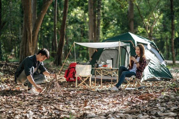 Jovem mando colhendo galhos e os juntando, preparando uma pilha de lenha para acampar à noite e uma linda namorada sentada na frente da barraca de acampamento
