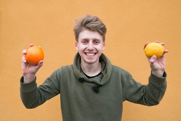 Jovem mantém limão e laranja nas mãos e sorrisos.