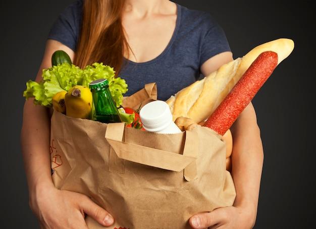 Jovem mantém saco com produtos diferentes