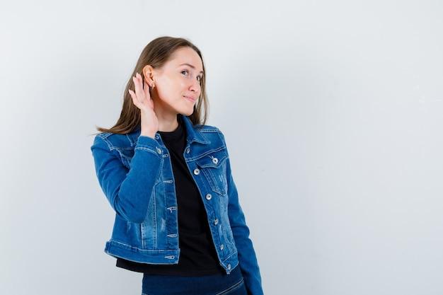 Jovem, mantendo a mão atrás da orelha na blusa, jaqueta e parecendo curiosa. vista frontal.